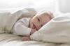 Lachendes Baby liegt auf dem Bett