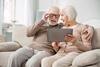 Älteres Paar sitzt auf dem Sofa und teilt sich ein Tablet