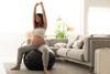 Schwangerefrau sitzt auf einem Gymnastikball