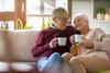 Älteres Paar trinkt gemeinsam einen Kaffee auf dem Sofa
