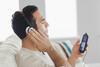 Ein Mann hört per Kopfhörer etwas auf seinem Mp3-Player