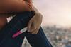 Junge Frau hält einen positiven Schwangerschaftstest in der Hand