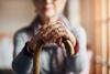 Seniorin hält einen Gehstock in den Händen.
