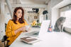 Frau sitzt mit Kaffeebecher am Schreibtisch und arbeitet an ihrem Laptop.