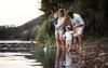 Familie steht an einem Fluss und schaut auf das Wasser.