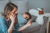 Mutter mit Fieberthermometer in der Hand.