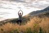 Frau macht Yoga auf einem Berg.