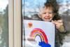 Kleiner Junge steht mit selbstgemalten Bild am Fenster.
