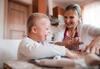 Kind mit Down-Syndrom backt lachend Plätzchen mit seiner Mutter