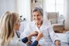 Pflegerin hilft Seniorin beim Zuknöpfen ihrer Bluse
