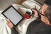 Älterer Mann mit Tablet und Kaffeebecher