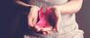 Frau hält pinke Schleife als Zeichen für Solidarität mit Brustkrebspatentinnen