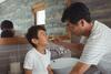 Vater und Sohn putzen zusammen Zähne