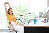 BGM: Junge Frau streckt sich am Arbeitsplatz