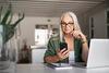 Beamte und Pensionäre: Frau sitz vor Ihrem Laptop und hält Ihr Smartphone in der Hand