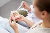 Frau beim Zahnarzt mit Modell-Implantat