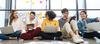 Studenten sitzen mit Laptops auf dem Boden