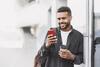 Junger Mann lehnt an einer Hauswand mit einem Kaffee und seinem Handy in der Hand