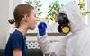 Arzt im Vollschutz testet eine junge Frau