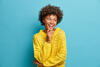 Frau lacht und steht vor blauem Hintergrund