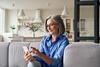 Arbeitnehmer: Frau sitzt mit ihrem smartphone in der Hand auf dem Sofa