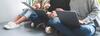 Teenager sitzen auf dem Boden mit Laptop auf dem Schoß