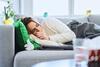 Frau liegt mit einer Erkältung auf dem Sofa