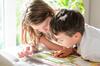 frau übt mit Jungen Lesen
