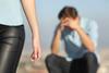 Mann sitzt im Hintergrund und hält die Hände vor sein Gesicht, Frau läuft weg