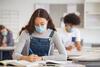 Aerosole: Mädchen sitzt mit Mund- und Nasenbedeckung im Klassenzimmer