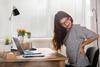 Junge Frau arbeitet am Schreibtisch und hält sich den Rücken