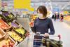 Frau betrachtet einen Apfel im Supermarkt