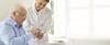 Ärztin erklärt einem älteren Herren eine Funktion auf einem Tablet