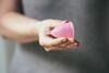 Frau hält Menstruationstasse in der Hand