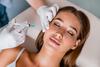 Junge Frau bekommt eine Injektion im Gesicht