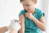 Impfung gegen Diptherie: Arzt impft kleinen Jungen im Oberarm