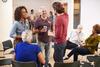 Gruppe von Menschen in einem Raum im Dialog