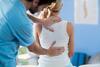 Berufserkrankung: Arzt tastet Patientin am Rücken ab
