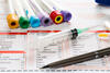 Blutbild: Blutentnahmeröhrchen liegen auf einem Datenblatt