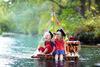 Kinder auf einem Floss im Fluss.