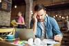 Kopfschmerzen: Mann sitzt in Cafe und hält sich am Kopf