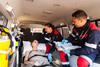 Frau mit 2 Rettungssanitätern im Krankenwagen