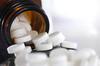 Tabletten aus einem Glasgefäß geschüttet