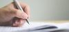 Nahaufnahme einer Hand mit Kugelschreiber beim Ausfüllen eines Dokuments