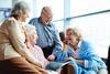 Vier Senioren sitzen zusammen und unterhalten sich