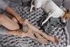 Krampfadern: Frau mit Stützstrümpfen und ihrem Hund auf dem Sofa