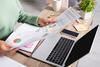 Laptop und Papiere auf Schreibtisch