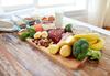 Servierplatte voller Lebensmittel wie Fleisch, buntem Gemüse, Eiern und einem Glas Milch