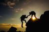 Ein Bergsteiger hilft seinem Kameraden beim Aufstieg.