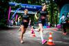 Zwei Läuferinnen auf der Laufstrecke vorm Startbogen mit BIG-Logo